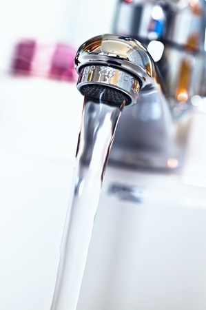 Water tap with flowing water on the sink in the bathroom