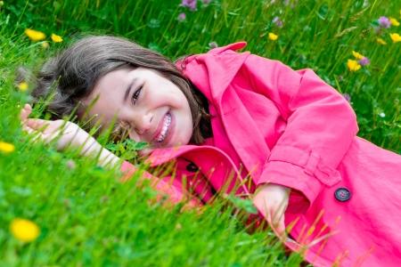 Sommer-Porträt von glücklichen hübsches kleines Mädchen, das im Gras von einem Blumengarten