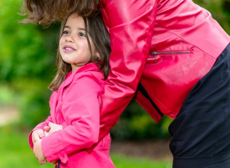 pretty little girl: Summer portrait of pretty little girl in the arms of his mother Stock Photo