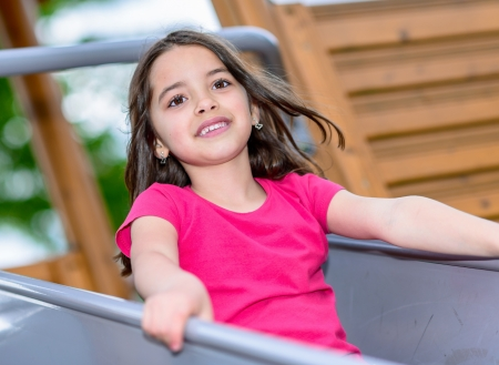 Natural portrait of a happy pretty little girl in playground photo