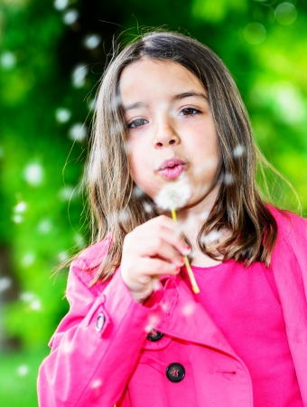 Summer portrait of cute child blowing on a flower standing in a park photo