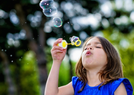 beautiful child blowing bubbles in a meadow with greenery in the background Stock Photo
