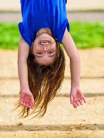 逆さまにぶら下がって、笑って、バック グラウンドで緑の美しい子供