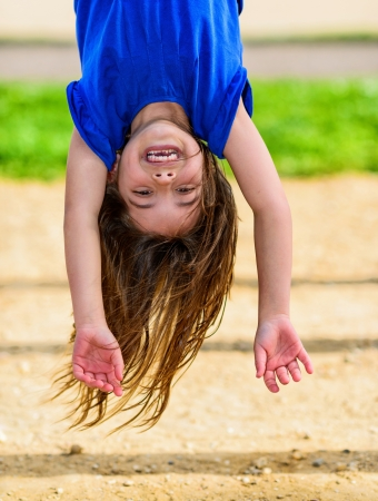 beautiful child hanging upside, laughing, with greenery in the background