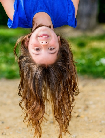 beautiful child hanging upside with greenery in the background