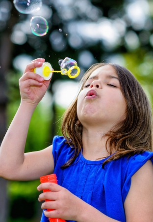 beautiful child blowing bubbles in a meadow  with greenery in the background