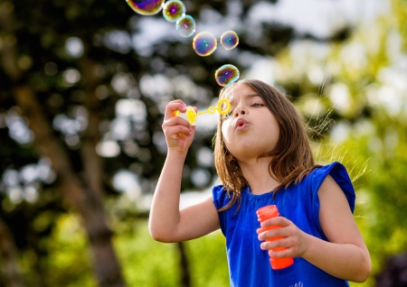 family outing: beautiful child blowing bubbles in a meadow  with greenery in the background