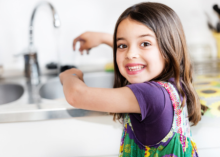 Expressive portrait of very cute girl washing hands photo