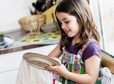 Expressive portrait of very cute girl wiping the dishes Banco de Imagens