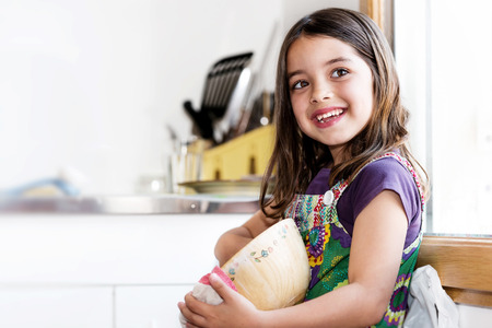 Expressive portrait of very cute girl wiping the dishes photo