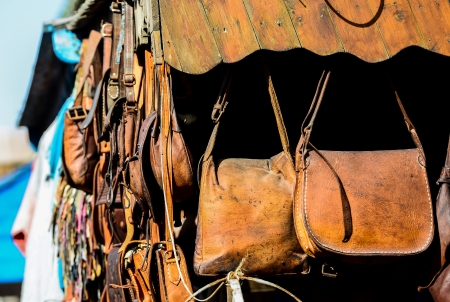 Leather bags on stall on the street market in Morocco photo
