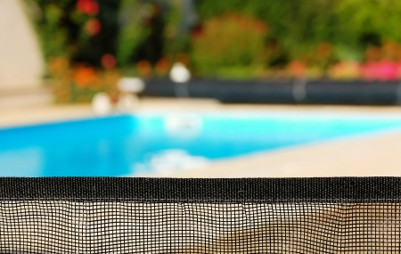 barrier for the safety of children with a pool in the background Stock Photo