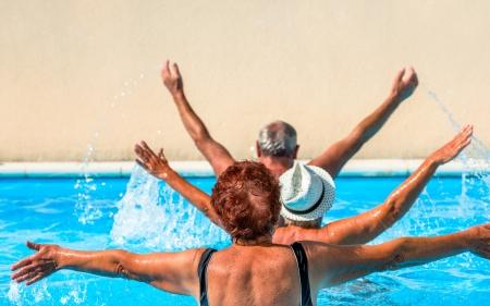 アクティブ シニア スイミング プールでエクササイズを取得