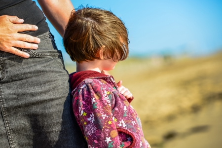 young child tight against her mother watching the sea beyond Stock Photo - 24213832