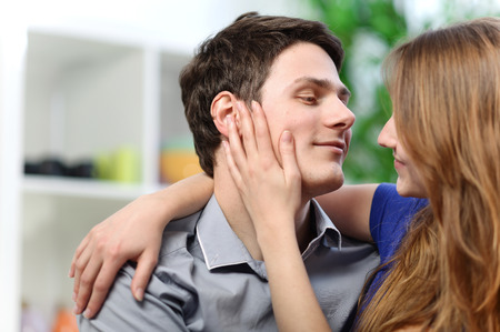 pretty woman stroking the cheek of her boyfriend with love photo