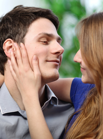 pretty woman stroking the cheek of her boyfriend with love