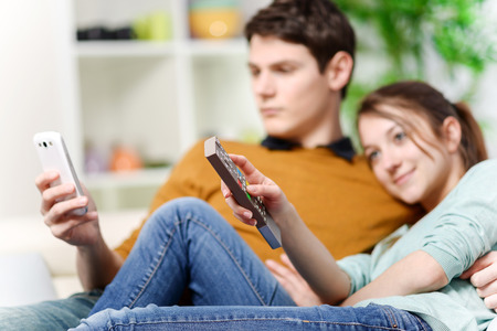 tv set: beautiful woman watching tv while her lover is watching a screen of cell
