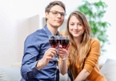 Very beautiful young couple toasting wine glasses photo
