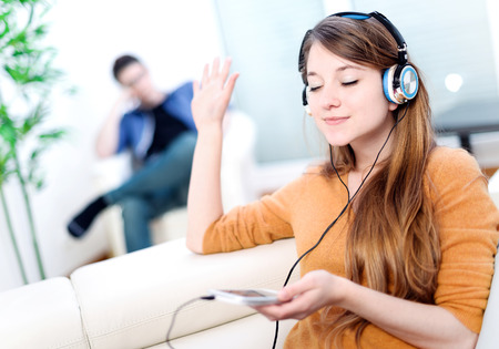 Beautiful blond listening to some music while her boyfriend is bored photo
