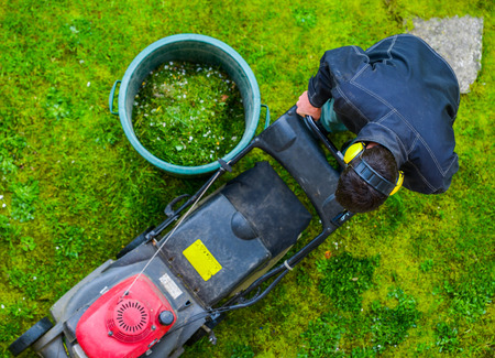 Gardener mowing the lawn in a park photo