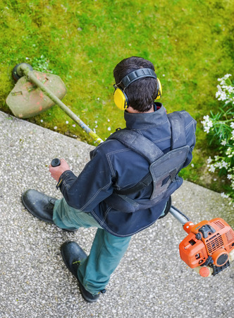 corded: gardener using corded string trimmer in a park