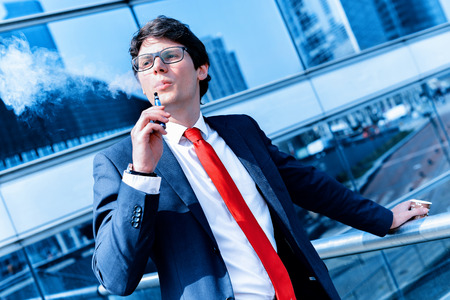 Cute young adult man inhaling from an electronic cigarette photo