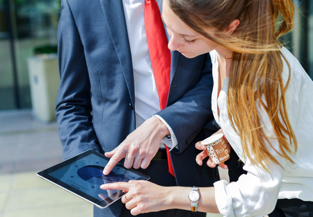 touchpad: Junior executives consulting a touchpad in front of their company
