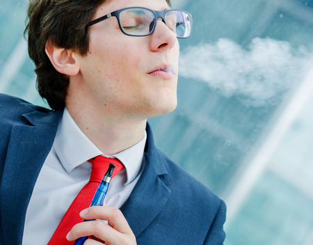 Portrait of cheerful man smoking with e-cigarette outdoor photo