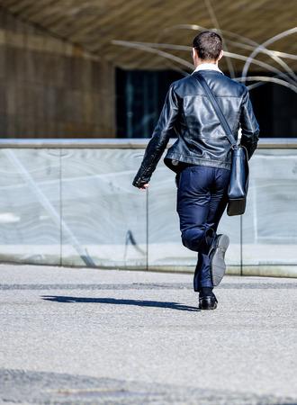 llegar tarde: Vista trasera de un joven hombre de negocios corriendo en la calle de la ciudad Foto de archivo