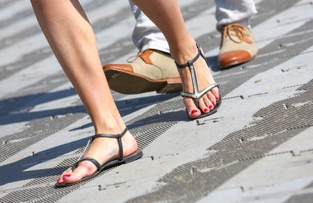 grope: closeup opposition about flip-flops and dress shoes