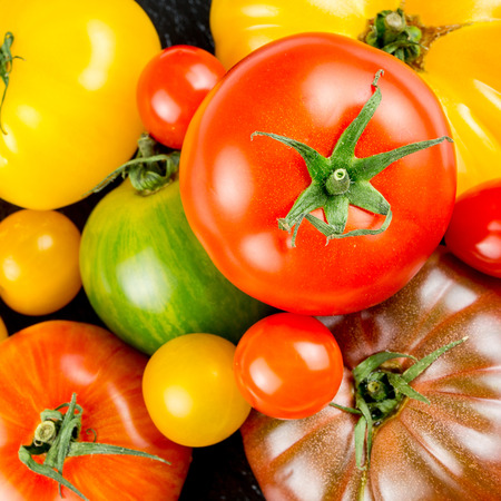 Closeup of varieties of colorful tomatos on slate plate Reklamní fotografie