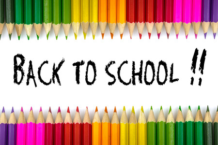 convivencia escolar: Bienvenido de nuevo a la escuela escrita en una hoja de papel escuela con plumas de colores