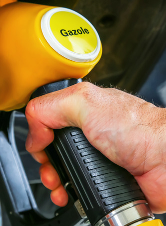 Driver pumping gasoline at the gas station, closeup photo