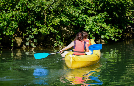 Two kids canoeing in a small bautifull lake which is surrounded by green nature and the reflections of the boat and the nature can be seen in the water