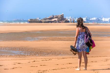 A beautiful young woman barefoot, wearing a summer dress and standing on the beach Standard-Bild