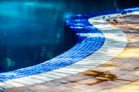 circling: Beautifully designed curvy line of blue and while tiles circling the sides of the swimming pool Stock Photo
