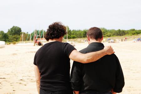 Dos amigos masculinos en ropa negra caminando por la playa con uno de ellos abrazando a la otra