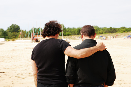 Two male friends in black clothes walking on the seaside with one of them hugging the other