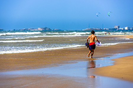 swimming shorts: A man in swimming shorts runing along the beach holding the rest of his clothing in his hands
