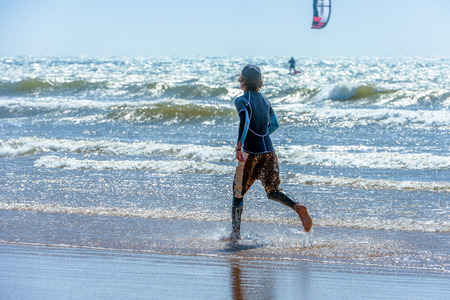 kiter: A young man in surfing clothing running along the seaside and watching a kiter on the waves in the background