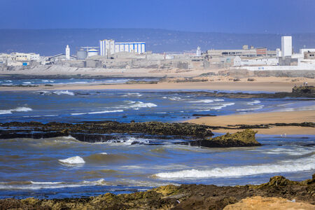 shipway: White industrial buildings in the distance on a piece of land surrounded by the sea and waves washing the rocks in the foreground Stock Photo