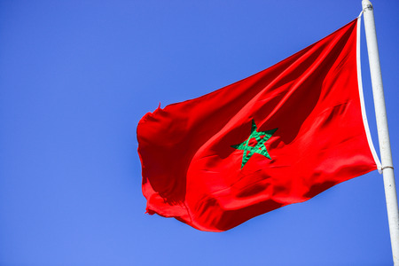 five pointed: Moroccan flag raised on a pole floating in the wind with clear blue sky in the background Stock Photo