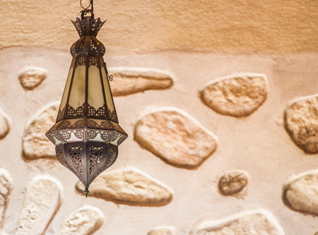 celling: A designed lamp with metallic ornaments hanging from the celling with a brick wall in the background