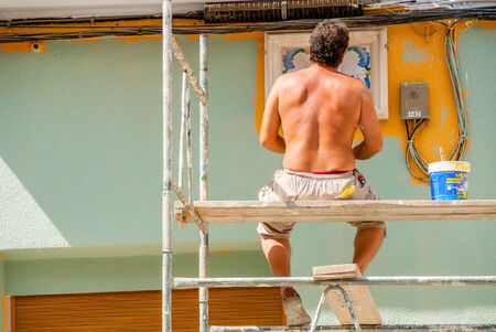 view of house painter in a street on a scaffolding photo