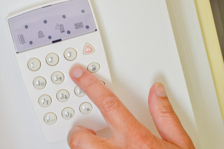 Hand is setting home security alarm system Stock Photo