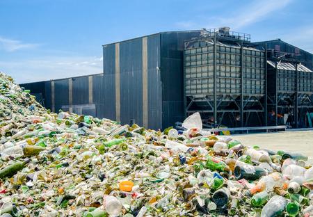 Heap of glass bottles near a recycling plant Editoriali