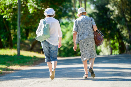 Mature womens walking together in a park photo