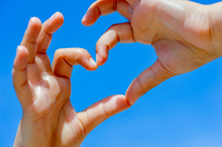 the loving  hands of a child who forms a heart directed toward heaven photo