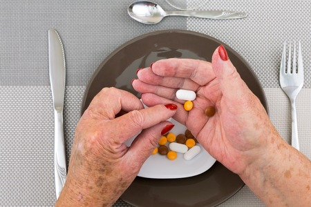 Red nailed elderly womans hands picking pills and capsules from a plate on dinner table photo