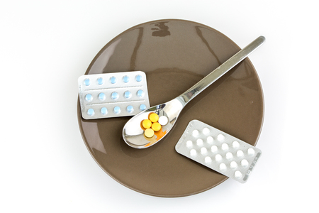 Still life on a plate with colorful pills in blishter packs and on a tea spoon with white background photo